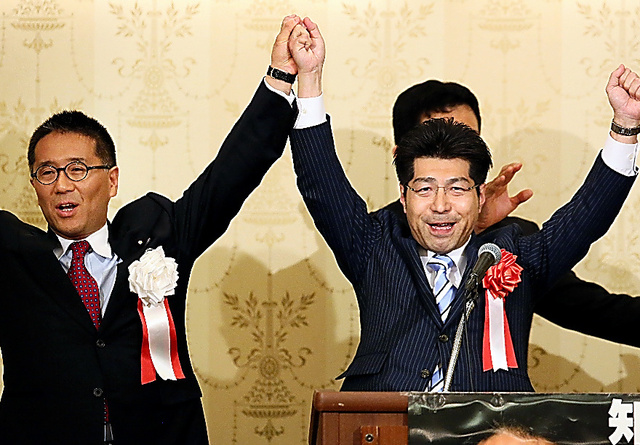 自民党の伊藤忠彦衆院議員(左)のパーティーで壇上に上がり、両手を掲げる公明党の里見隆治氏=14日、名古屋市中区、細川卓撮影