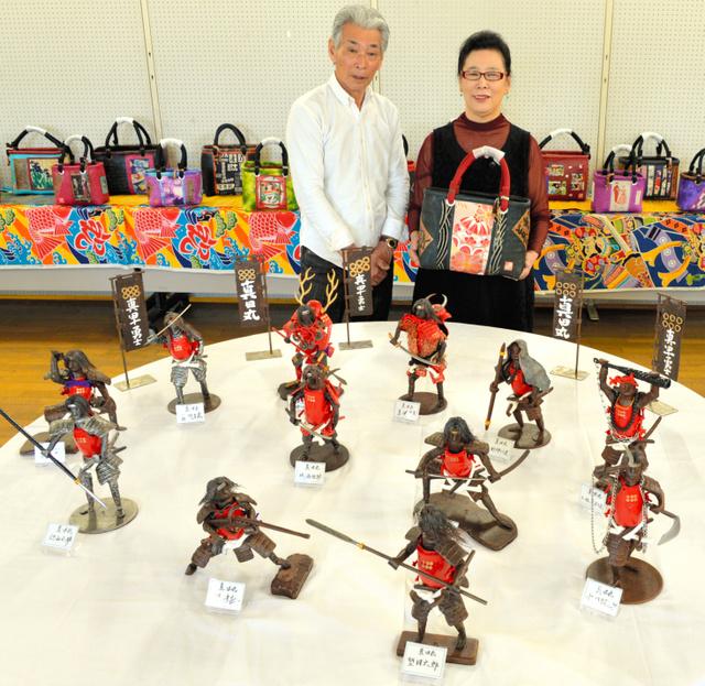 「真田十勇士」の人形を作った石橋鉄心さんと、一閑張りのバッグを持つ有吉ゆかりさん=行橋市