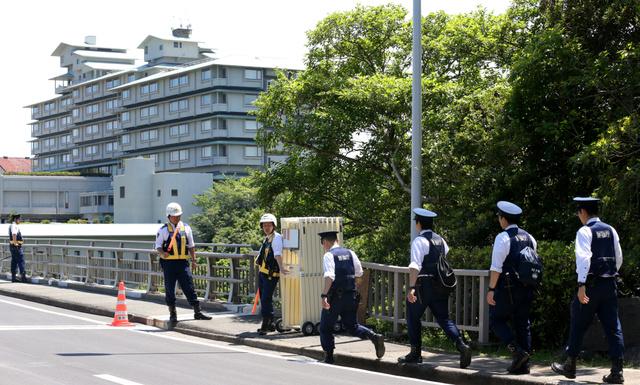 志摩観光ホテル(左)の周辺では、大勢の警察官が警備に当たっていた=18日午後、三重県志摩市、吉本美奈子撮影