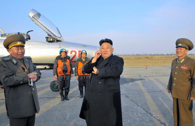 朝鮮人民軍の飛行訓練を指導する金正恩氏。朝鮮中央通信が2014年3月17日報じた=朝鮮通信。たばこを手にしているとして話題になった