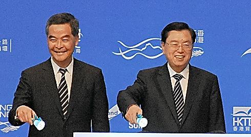 経済フォーラムの開幕式で、香港の梁振英行政長官(左)と並ぶ張徳江氏=18日
