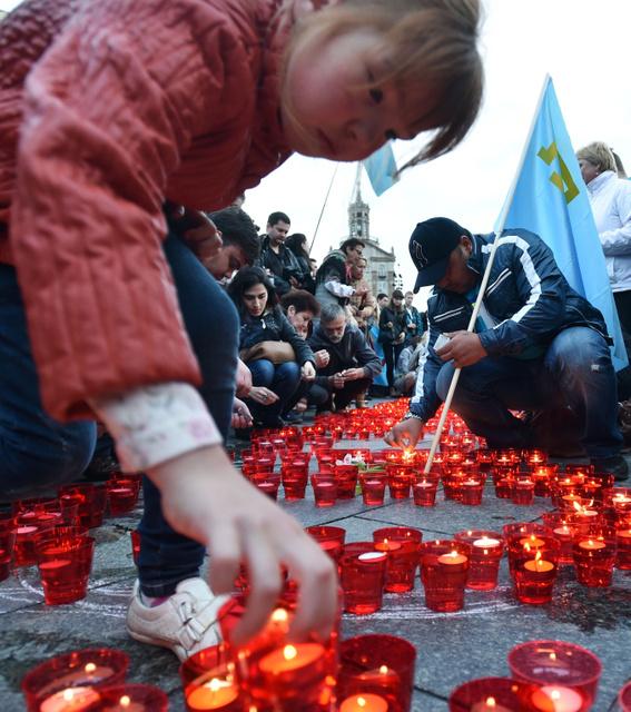 ウクライナの首都キエフで18日、クリミア・タタール系住民が72年前のタタール人追放の追悼集会を開き、キャンドルに火をともした=AFP時事。この日は、ロシアが併合したクリミア半島でも集会が行われた