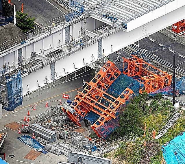 新名神高速の工事現場で支柱が倒れ、有料道路をふさいでいた=19日午後、大阪府箕面市、本社ヘリから、伊藤進之介撮影