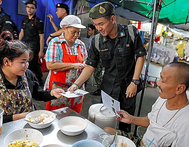 タイの首都バンコクでは4月19日、軍の学校の生徒が、8月に実施される新憲法案の国民投票で投票するよう市民らに呼びかけて小冊子を配った=ロイター