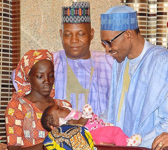 ナイジェリアの首都アブジャで19日、イスラム過激派「ボコ・ハラム」に誘拐され、初めて救出されたとされる女子学生(左)と面会するブハリ大統領(右)=AP。女子学生は生後4カ月の娘を抱いて面会した。ナイジェリア軍は同日、別の女子学生も救出されたと発表した。200人以上の女子学生が依然として行方不明となっている