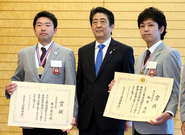 国際アビリンピックで金メダルを取った香川貴宏氏(左)、柳本佑氏(右)に表彰状を渡し、記念撮影におさまる安倍晋三首相=20日午前11時30分、首相官邸、飯塚晋一撮影