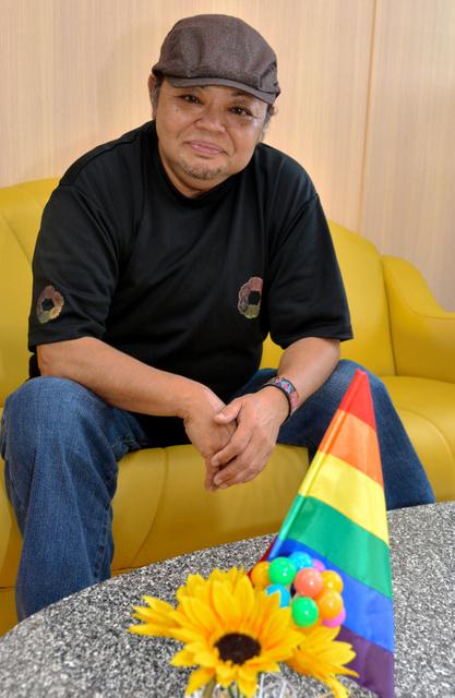 性の多様性を象徴するレインボーフラッグを前に座る「レインボーポート向日葵」の会長正貴さん=指宿市東方