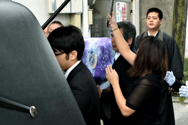 家族に抱えられ出棺される被害者の女性=21日午前9時9分、沖縄県名護市、吉田拓史撮影
