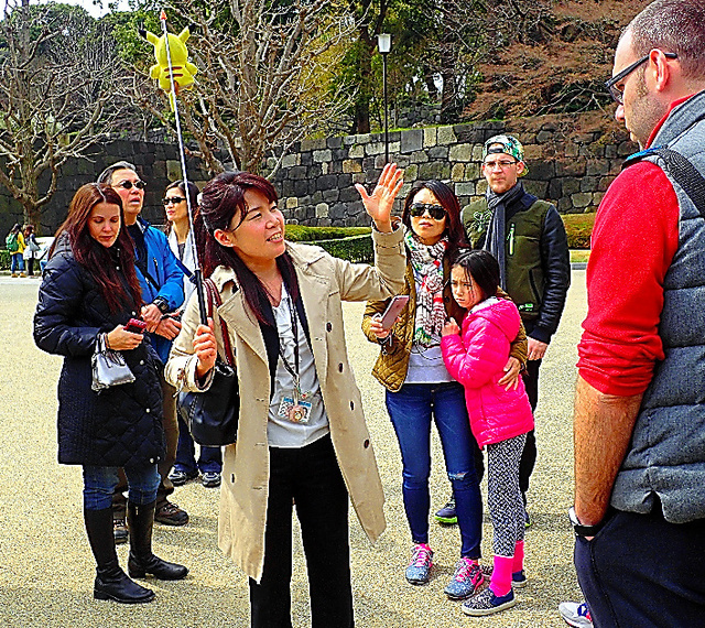 外国人観光客らを案内する通訳案内士の坂野美奈子さん(中央)=皇居