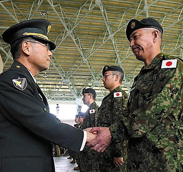 壮行会で田浦正人師団長(左)と握手をかわす隊員=21日午前、陸自東千歳駐屯地