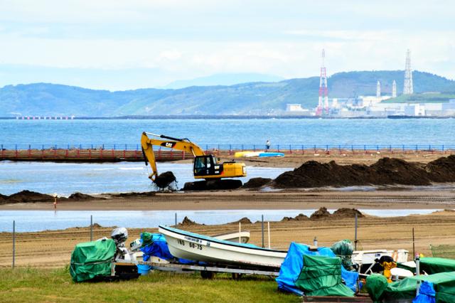 花火打ち上げ会場の海面にできた砂州の浚渫(しゅんせつ)工事。砂はボートのある砂浜側に移す=柏崎市西港町