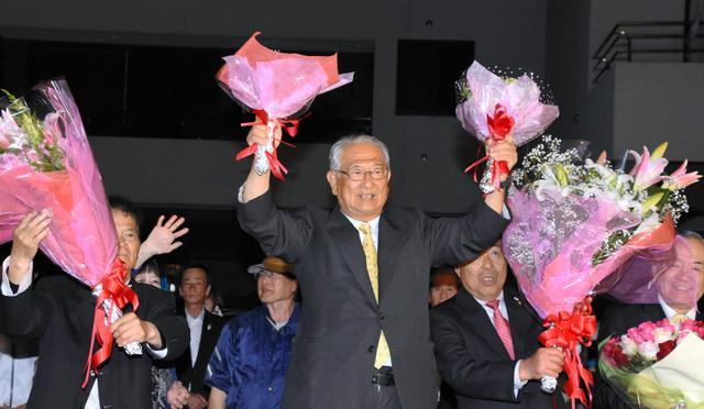 7選を決め、花束を掲げる柏木征夫氏(中央)=22日夜、和歌山県御坊市島、浅沼愛撮影
