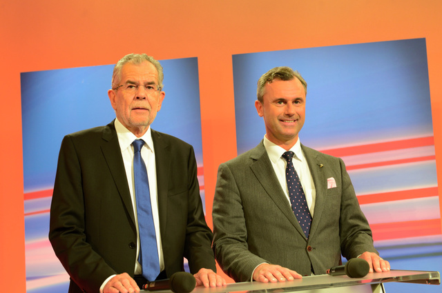 ウィーンで22日、オーストリア大統領選の開票中にそろってテレビに出演したホファー氏(右)とファンダーベレン氏=喜田尚撮影