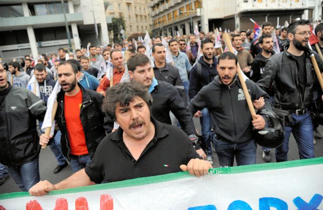ギリシャのアテネで22日、国会で可決された財政改革法案に反対するデモの参加者ら=ロイター