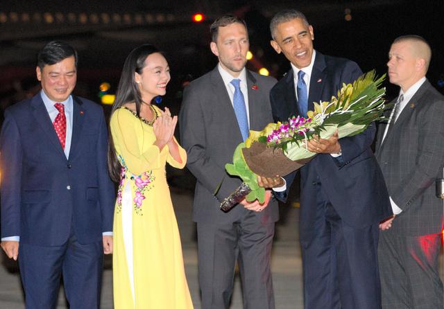 ベトナムのハノイで22日、空港に到着して女性から記念の花束をもらうオバマ米大統領(右から2人目)=AP