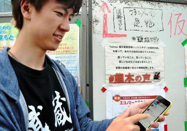 車中泊の避難者が多く集まる大型展示場「グランメッセ熊本」で、運営するツイッターのアカウント「熊本現地情報」を確認する米山凱一郎さん。ホワイトボードには、被災者にハッシュタグ「#熊本の声」をつけてつぶやくよう呼びかけるチラシを貼った=4月28日、熊本県益城町