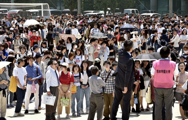 訓練で屋内からグラウンドに避難した熊本学園大の学生や教職員たち。日傘やタオルで暑さをしのぐ学生の姿も見られた=23日午前11時53分、熊本市中央区、福岡亜純撮影