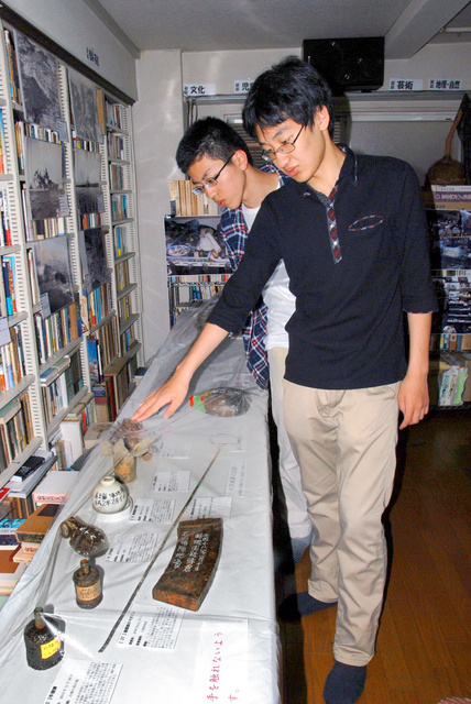 展示された遺品について説明する生徒会長の西尾慧吾さん(右)=大阪市大正区