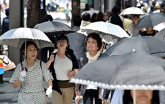 東京・銀座では、日傘をさして歩く人の姿が多く見られた=23日午前11時2分、恵原弘太郎撮影