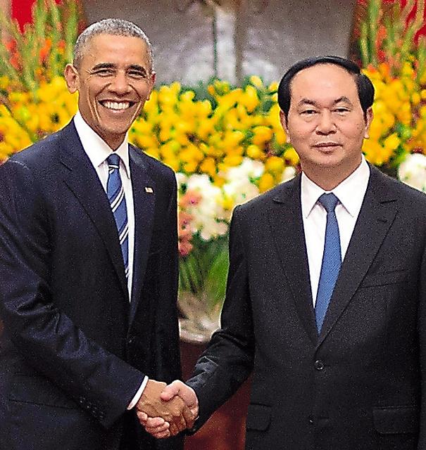 ハノイで23日、ベトナムのチャン・ダイ・クアン国家主席(右)と握手を交わすオバマ米大統領=AFP時事