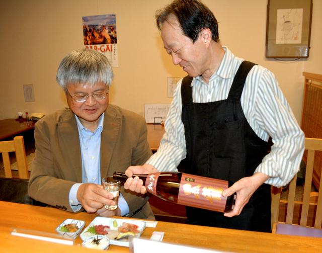 日本酒を飲みながら平和寄席の打ち合わせをする石川千春さん(右)と二杯亭小酔楽さん=函館市元町の居酒屋「元町九条」