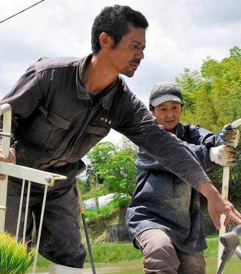 田植え機を操る永田ユキオさん(左)と妻の聖子さん=栗原市一迫片子沢
