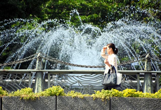 強い日差しを受け、手をかざして歩く女性=岡山市北区の西川緑道公園