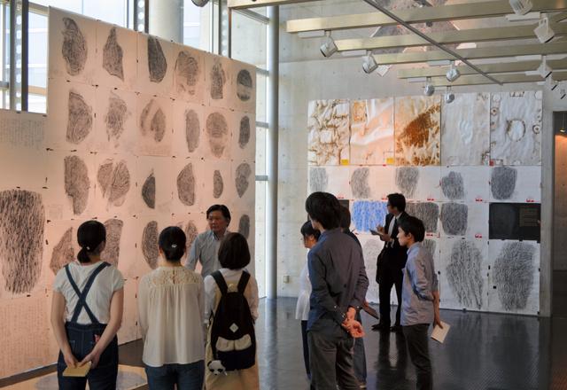 「被爆樹×被曝し続ける樹、他」(フロッタージュ作品)を前に学生たちに作品を説明するプロジェクト関係者=長岡造形大1階ギャラリー