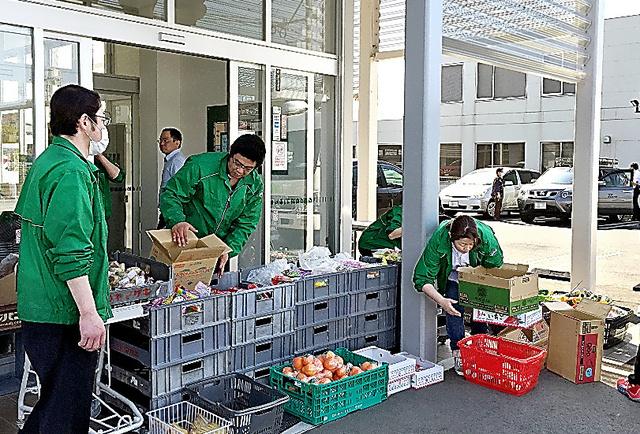 スーパーの入り口でパンや果物、おむつなどを住民に無料配布した=4月15日、「よかもんね!」ましき店提供