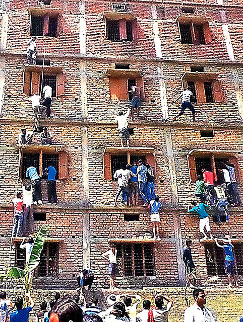 インド東部ビハール州で2015年3月、受験生にカンニングペーパーを渡すため校舎をよじ登る家族ら=AP