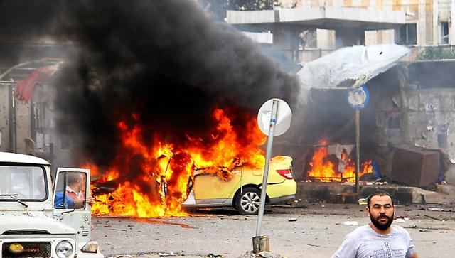 シリアの港湾都市タルトスで23日、自動車が爆発した現場。シリア国営通信が配信した=AP