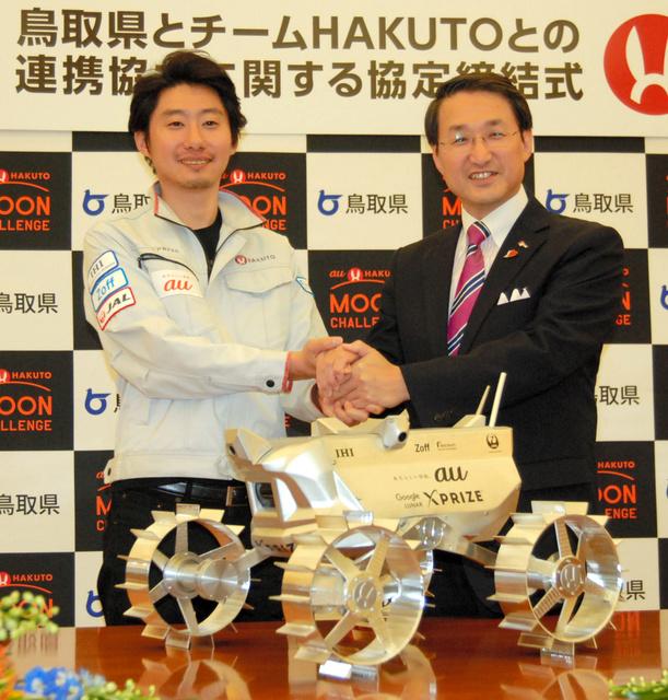 月面探査車の試作機を前に握手する袴田代表(左)と平井知事=鳥取市の知事公邸