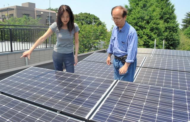 店舗兼住宅の屋上に設置した太陽光パネルについて話す原尚美さん(左)と田島和夫さん=練馬区栄町