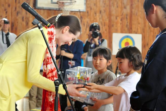 子どもたちから折り鶴が入ったケースを受け取るナターシャ・グジーさん(左)=会津若松市河東町大田原の大熊町立熊町・大野小学校