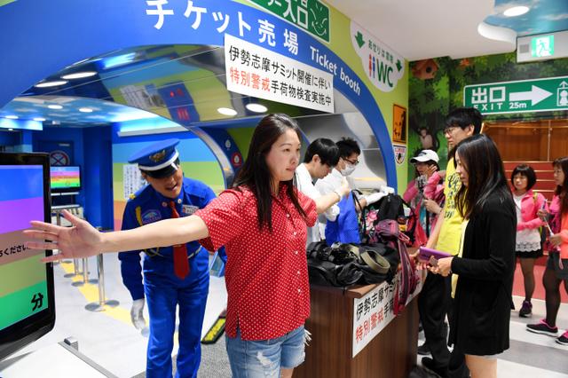 伊勢志摩サミットの開幕を前に、大阪市浪速区の通天閣では入場者の手荷物検査をしている。訪れた観光客が地下のチケット売り場の前でかばんを広げ、金属探知機による検査を受けていた。特別警戒は27日まで続き、一部のゴミ箱やコインロッカーも閉鎖している。通天閣の下でたばこ屋を営む女性は「(サミット会場との)距離は関係あれへん。世界中からお客さんが来るから検査したら私らでも安心できる」と話した=25日午前10時16分、大阪市浪速区、伊藤進之介撮影