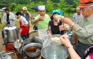 コック帽の西据廣さん(中央)の助言を受けながら、うどん作りの流れを確認する参加者ら=佐賀市大和町梅野