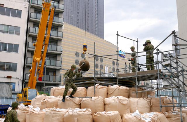"""不発弾撤去のため設置された土<Asajikai sjis=""""嚢"""">囊</Asajikai>。市は「慣例」で土地所有者に費用の負担を求めた=2015年5月9日、大阪市浪速区"""