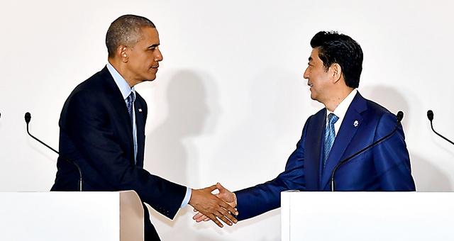 日米首脳会談後の共同記者会見を終えて握手をするオバマ米大統領(左)と安倍晋三首相=25日午後11時32分、三重県志摩市、代表撮影
