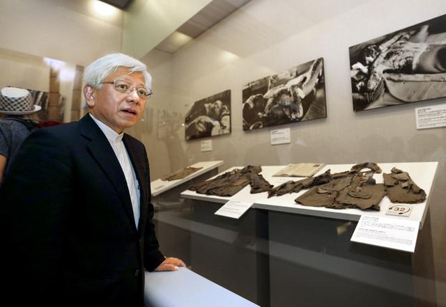 遺品を前にする広島平和記念資料館の志賀賢治館長=広島市中区、青山芳久撮影