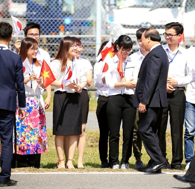 中部空港に到着し、在日のベトナム人らの出迎えを受けるベトナムのフック首相(右から2人目)=26日午後2時18分、愛知県常滑市、内田光撮影