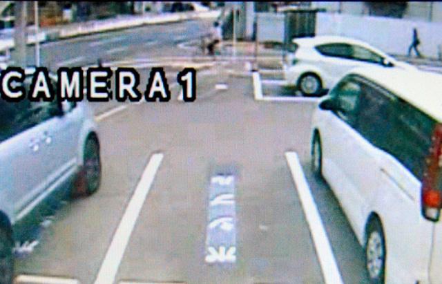 事件直後、自転車で逃走する白いシャツの男(画面奥)が、郵便局から約50メートル東にある防犯カメラに映っていた=26日午後2時40分ごろ、堺市堺区三宝町4丁、読者提供