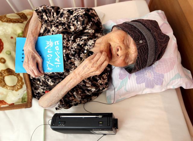 愛用のラジオでオバマ米大統領が参加している伊勢志摩サミットのニュースを聴く佐伯敏子さん。手にするのは自身の体験記=27日午前、広島市東区、青山芳久撮影