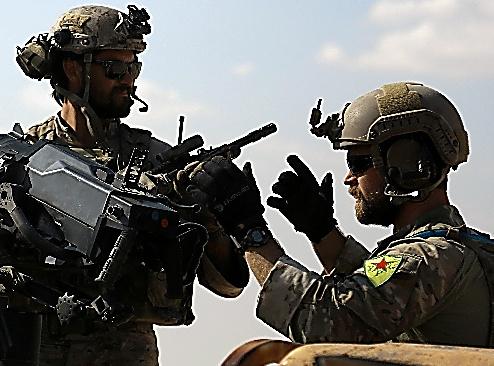 シリア北部で25日、クルド系武装組織の記章を腕につける米特殊部隊兵士とされる男性(右)=AFP時事