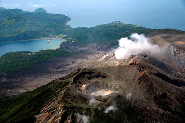 全島避難となった新岳の爆発的噴火から1年を迎える口永良部島。噴火警戒レベルは「5」を維持したままだ。中央左奥は本村地区=26日午後、鹿児島県屋久島町、朝日新聞社ヘリから、森下東樹撮影