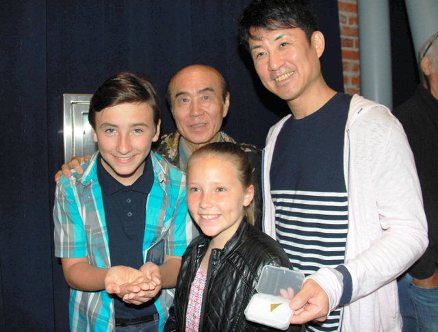 禎子さんの折った鶴を手に乗せる米国の少年(左)と佐々木雅弘さん(後列中央)、佐々木祐滋さん=28日、ロサンゼルス、平山亜理撮影