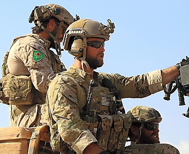 シリア北部のラッカ近郊で25日、トラックの荷台に乗る米特殊部隊兵士ら=AFP時事。左後方の兵士がつけている記章は、YPGの女性部隊である「YPJ」のもの