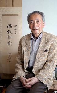 父、樋口盛一さんが大切にしていた掛け軸と。「温故知新。学者はそういう仕事だ。新しいことばかりちゃらちゃら追わずにね」=浅野哲司撮影