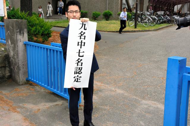 新潟地裁の判決で、原告9人中7人の請求を認めたことを知らせる紙を持つ弁護団の弁護士=30日午後3時すぎ、新潟市中央区、川村貴大撮影