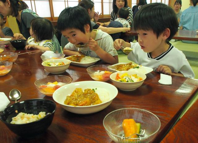 カレーをほおばる子どもたち=和光市新倉の満願寺