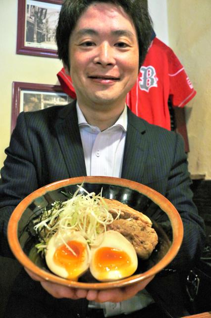 職場体験学習の中学生が考案した「角煮丼」を持つ樋口克則店長=神戸市東灘区森北町2丁目